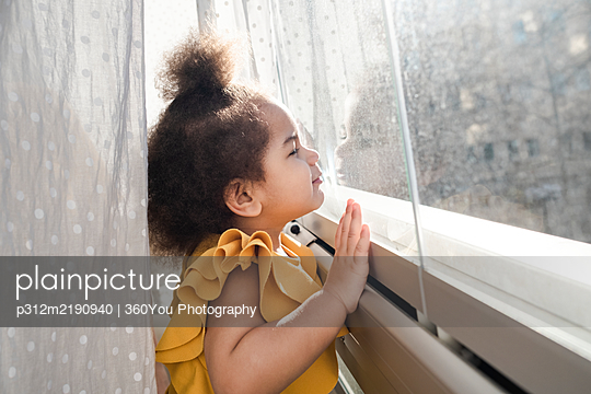 Girl looking through window - p312m2190940 by 360You Photography