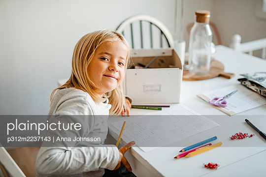 Smiling girl at home doing homework - p312m2237143 by Anna Johnsson