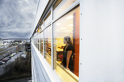 View of woman standing looking out of window, Reykjavik, Iceland - p1084m1036858 by GUSK