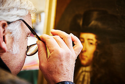 Man with glasses looks at the portrait of a painting in an exhibition - p1312m2082183 by Axel Killian