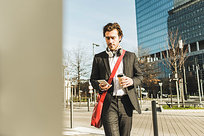Germany, Frankfurt, Young businessman walking the city with cup of coffee, using mobile phone - p300m1115300f by Uwe Umstätter