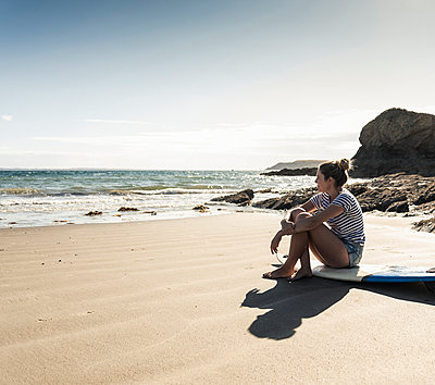 Young woman sitting on her surfboard on the beach, looking at the sea - p300m2081522 by Uwe Umstätter