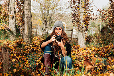 Smiling woman photographing through camera while sitting amidst autumn leaves by dog - p300m2276956 by Manu Reyes