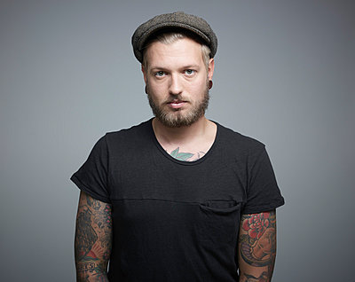 Portrait of young man with tattoos against grey background, close up - p300m879170 by Rainer Holz