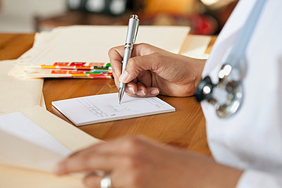 Doctor writing out prescription. - p328m717982f by Hero Images