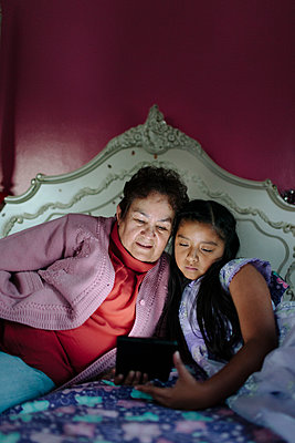 Hispanic grandmother and granddaughter using digital tablet on bed - p555m1409596 by Shestock