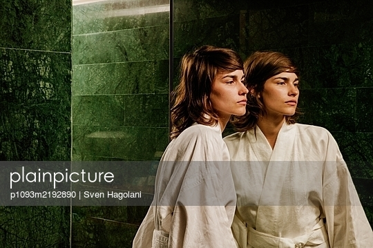 Young woman in bathrobe in front of a mirror, portrait - p1093m2192890 by Sven Hagolani