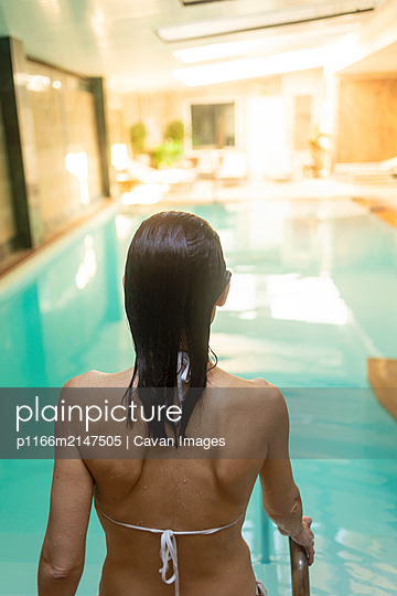Rear view of a latin wet woman with swimwear walking to pool in a spa center - p1166m2147505 by Cavan Images