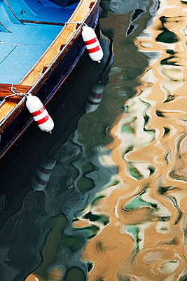 Reflections of Building on Canal Boat in Venice - p1100m2205916 by Mint Images