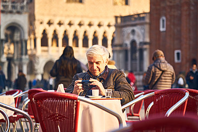 Man sitting in sidewalk cafe and looking at his photos on his digital camera - p1312m2082195 by Axel Killian