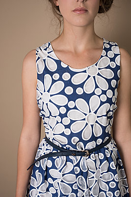 Young woman wearing a sleeveless blue and white dress with large, graphic floral pattern. - p1433m1574952 by Wolf Kettler