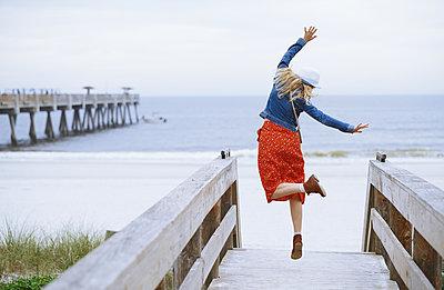 Woman dancing on the wooden boardwalk - p1577m2150313 by zhenikeyev