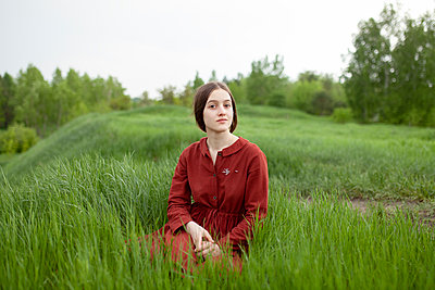 Woman in red dress on a meadow - p1646m2264065 by Slava Chistyakov