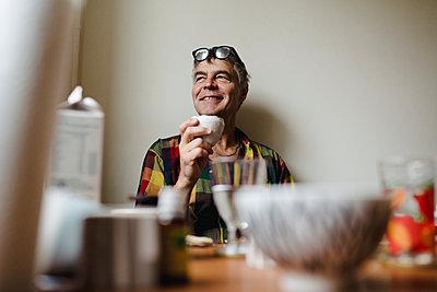 Smiling man at table - p312m2162052 by Stina Gränfors