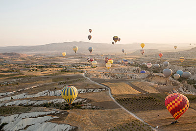 Large group of hot air balloons floating above field landscape, Cappadocia, Anatolia,Turkey - p429m1022612 by Guido Cavallini