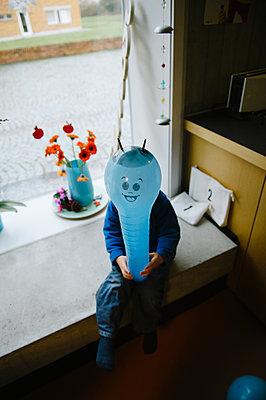 Kleiner Junge mit blauem Luftballon - p819m1065056 von Kniel Mess