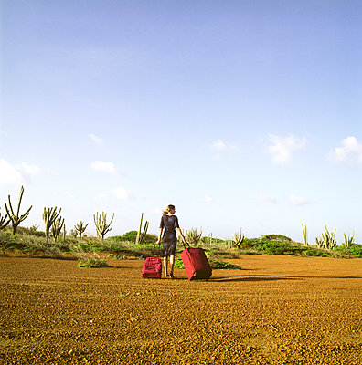 Woman with suitcases lost in desert - p1231m1043044 by Iris Loonen