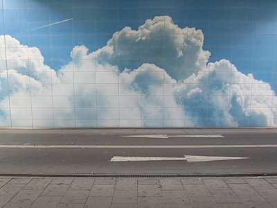 Road with directional arrows and clouded sky on wall - p1590m2224790 by marion blomeyer