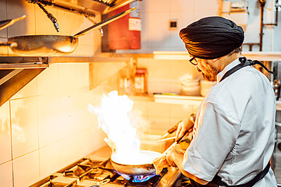Indian chef flambing food in restaurant kitchen - p300m2166914 by Oscar Carrascosa Martinez