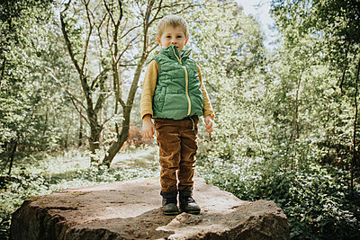 Cute boy standing on boulder in forest - p300m2276418 by Mareen Fischinger