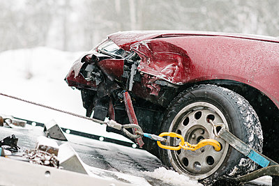 Damaged maroon car on tow truck during winter - p426m1451693 by Helena Wahlman