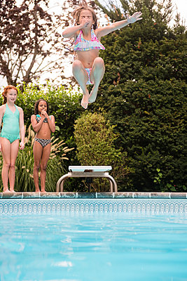 Girl holding nose jumping off diving board into swimming pool - p555m1303493 by JGI/Jamie Grill