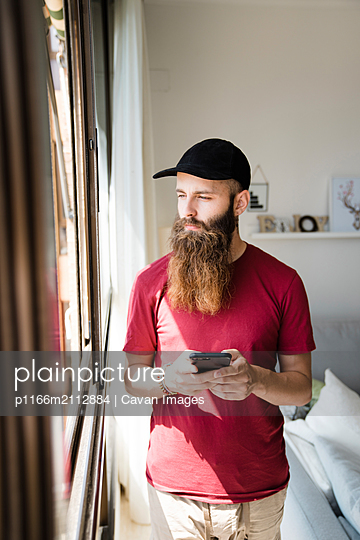 Thoughtful hipster man looking through window while holding mobile phone at home - p1166m2112884 by Cavan Images