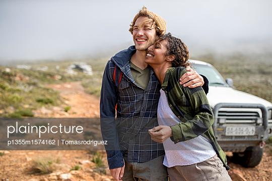 Junges Paar auf Bergtour mit SUV im Hintergrund - p1355m1574162 von Tomasrodriguez
