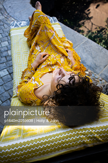 Woman lying on the sun lounger by the pool - p1640m2259938 by Holly & John