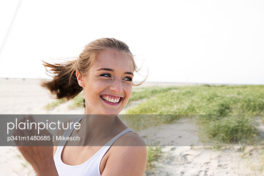 Happy young woman on St. Peter Ording beach  - p341m1480685 by Mikesch