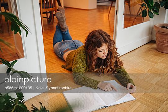 Junge Frau liest in einem Buch  - p586m1200135 von Kniel Synnatzschke