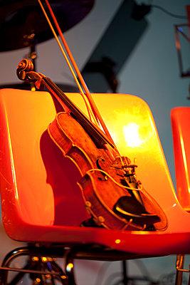 Geige auf orangenem Stuhl - p1579m2158088 von Alexander Ziegler