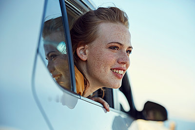 Smiling young woman looking out of a car - p300m1460295 by Martina Ferrari