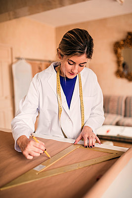 Female tailor using ruler while measuring fabric on workbench - p300m2293486 by LUPE RODRIGUEZ