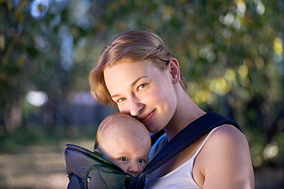 A mother with her baby in a baby carrier, portrait - p30110660f by Vladimir Godnik