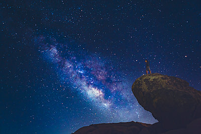 USA, California, Joshua Tree National Park, Man standing on rock and looking at Milky Way - p352m1350124 by Eija Huhtikorpi