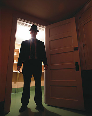 Man in suit stands in doorway - p3720309 by James Godman