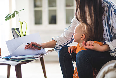 Midsection of working mother examining documents with baby girl at home office - p426m2117042 by Maskot