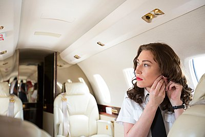 Female flight attendant putting on earring in cabin of private jet - p924m1081779f by Raphye Alexius