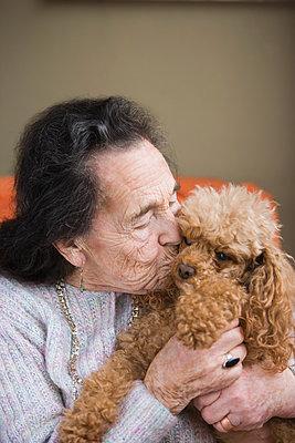 Senior woman kissing dog - p924m896174f by REB Images