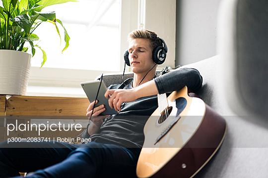 plainpicture - plainpicture p300m2083741 - Relaxed young man with tabl... - DEEPOL by plainpicture/Robijn Page