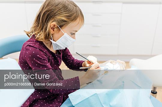 Girl at the dentist examining teddy bear - p300m2166598 von Daniel González