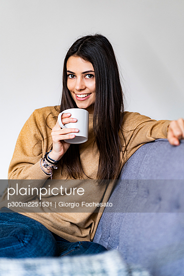 Woman drinking coffee while sitting on sofa at home - p300m2251531 by Giorgio Fochesato