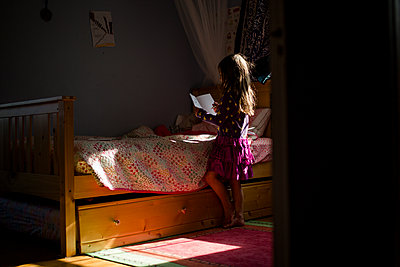 A small girl stands in her bedroom writing in a journal - p1166m2096623 by Cavan Images