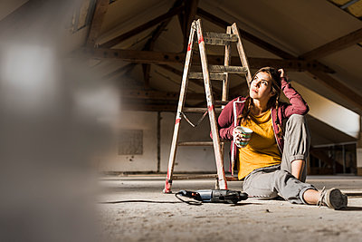 Independent young woman renovating her new home, sittiing on floor with cup of coffee - p300m1356270 by Uwe Umstätter