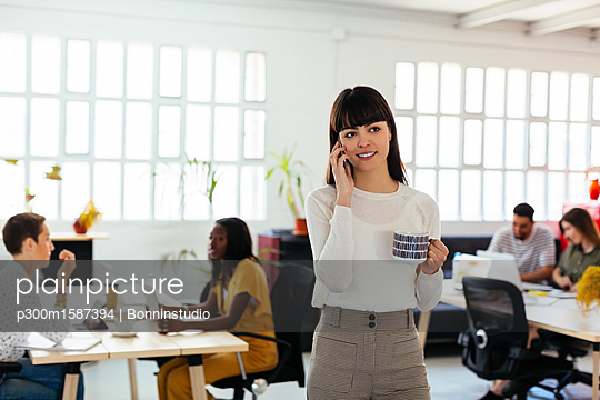 Portrait of smiling young woman on cell phone in office with colleagues in background - p300m1587394 von Bonninstudio