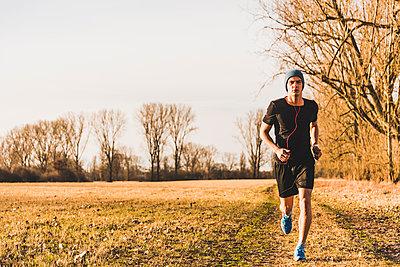 Man running in rural landscape - p300m1356351 by Uwe Umstätter