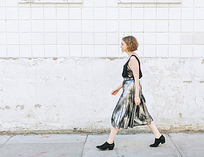 Woman in metallic skirt walking in street, full length, side view - p429m1569681 by Lena Mirisola