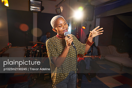 Young female musician singing into microphone in recording studio - p1023m2190245 by Trevor Adeline