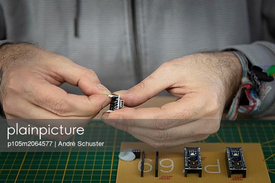 Elektriker hält ein elektronisches Bauteil - p105m2064577 von André Schuster